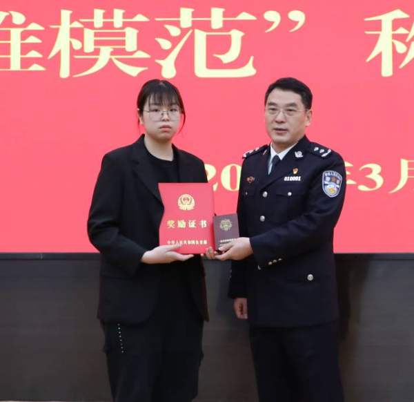 """李世全女儿接受广州市副市长、市公安局局长孙太平为李世全颁发的""""一级英模""""奖章、证书。"""
